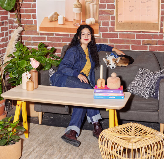 A woman is sitting on a sofa at the lounge of her small business.