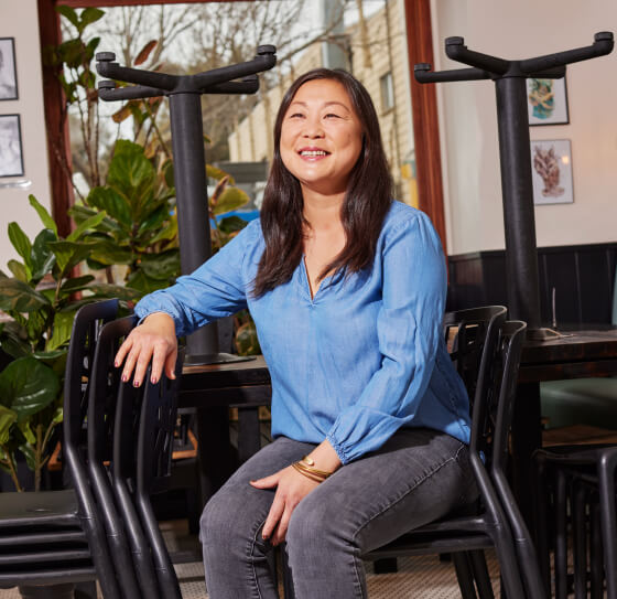 A restaurant owner is laughing while sitting on a chair at her restaurant.