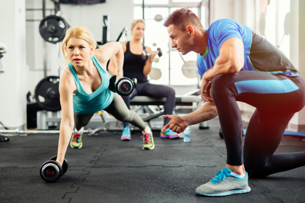 Personal trainer helping client