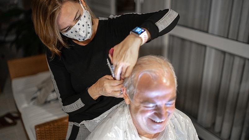 A woman cuts a man's hair.